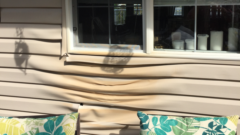 Vinyl siding completely ruined due to a barbeque grill left unattended.